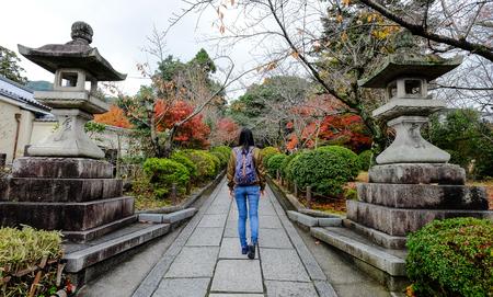 momiji: A tourist walking at autumn garden in Kyoto, Japan.