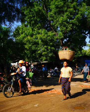 selling service: Yangon, Myanmar - Oct 19, 2015. Burmese woman walking on rural road in Yangon, Myanmar. Yangon is the country largest city with a population above seven million.