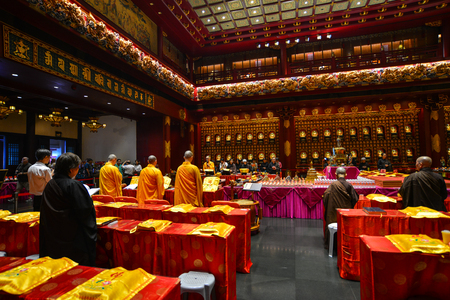 Singapore - Jun 12, 2017. Monks praying at Tooth Relic Temple in Singapore. The remarkable temple, in the heart of Singapore Chinatown, has much to interest its visitors.