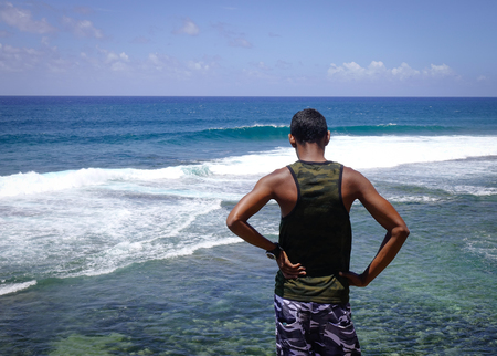 An African man looking at the sea in Le Morne, Mauritius. Mauritius is a major tourist destination ranking 3rd in the region and 56th globally.