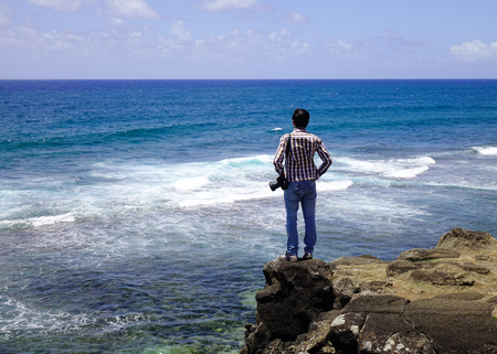 A man looking at the sea in Le Morne, Mauritius. Mauritius is a major tourist destination ranking 3rd in the region and 56th globally.