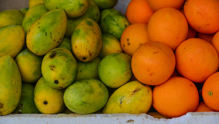 Mango and orange fruits at the rural market in Coron Island, Philippines.