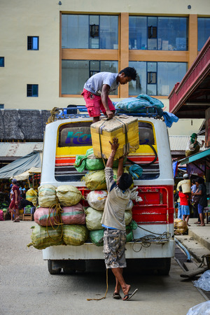 Coron, Philippines - Apr 4, 2017. People loading goods to the bus in Coron Island, Philippines. Coron is the third-largest island in the Calamian Islands in northern Palawan. Editorial