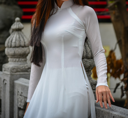 An Asian woman in Vietnamese traditional dress (called Ao Dai) at Chinese pagoda in Hong Kong.