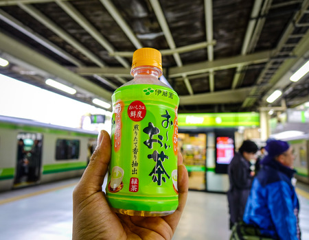 Nagoya, Japan - Dec 3, 2016. Hand holding a bottle of Japanese tea at JR station in Nagoya, Japan. Nagoya, capital of Aichi Prefecture, is a manufacturing and shipping hub in Honshu. Editorial