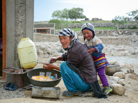 Leh, India - Jul 21, 2015. A Tibetan woman with her son at a village in Nubra Valley, India. 65% of children attend school but absenteeism of both students and teachers remains high.