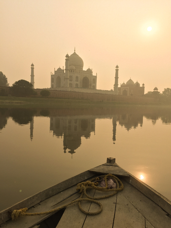 Taj Mahal at sunset in Agra, India. View from the boat on Yamuna River.