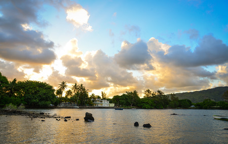 Sunset on the sea with palm trees in Mahebourg, Mauritius.