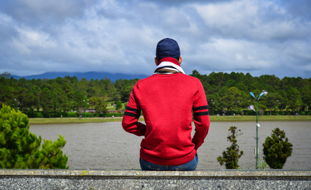 An Asian man sitting and looking the lake in Dalat Highlands, Vietnam. Stock Photo