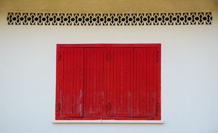 Red wooden window on the old wall of Wat Chalong in Phuket, Thailand.