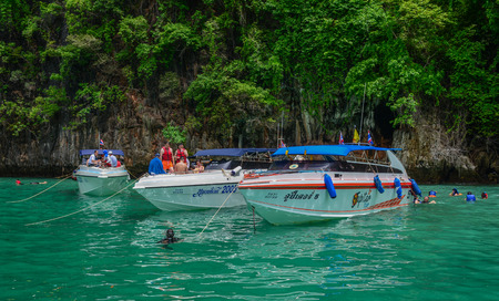 Phuket, Thailand - Jun 19, 2016. Tourist speedboats docking on the blue sea in Phuket, Thailand. Phuket consists of the island of Phuket, and another 32 smaller islands off its coast.