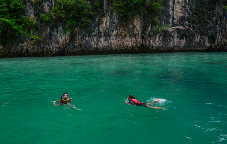 Phuket, Thailand - Jun 19, 2016. Tourists swimming on the blue sea in Phuket, Thailand. Phuket consists of the island of Phuket, and another 32 smaller islands off its coast.