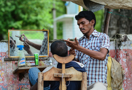Bodh Gaya, India - Jul 9, 2015. Street barber at downtown in Bodhgaya, India. Bodhgaya (Bodh Gaya) is the site of the Buddha enlightenment and the holiest of 4 main Buddhist.