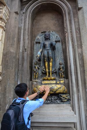 A young man praying at Mahabodhi Temple in Bodh Gaya, India. Editorial