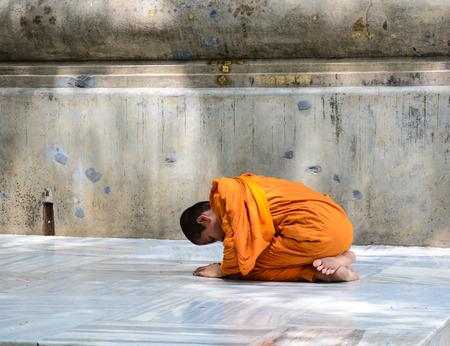 A novice praying at Mahabodhi Temple Complex in Bodhgaya, India.