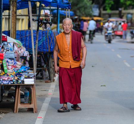Bodhgaya, India - Jul 9, 2015. A Buddhist monk walking on street in Bodhgaya, India. Bodh Gaya is considered one of the most important Buddhist pilgrimage sites. Editöryel