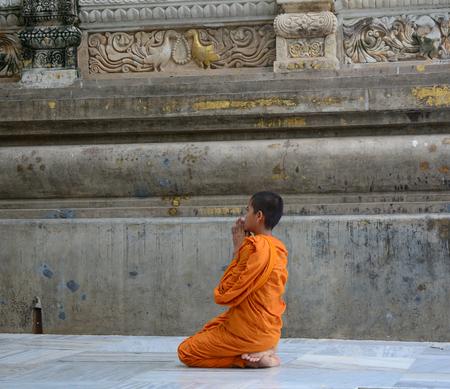 A novice monk praying at Mahabodhi Temple in Bodhgaya, India.