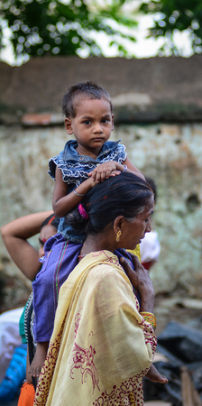 Bodhgaya, India - Jul 9, 2015. A woman with her son on street in Bodhgaya, India. Bodh Gaya is considered one of the most important Buddhist pilgrimage sites. Editorial