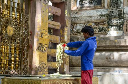 Bodhgaya, India - Jul 9, 2015. A man praying at Mahabodhi Temple in Bodhgaya, India. Mahabodhi marking the spot of the Buddha enlightenment. Editorial