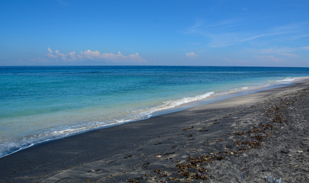 Black sand beach with blue sea at summer on Lombok Island, Indonesia. Stock Photo