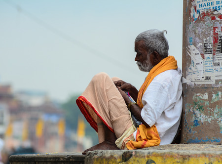 Varanasi, India - Jul 12, 2015. An old man sitting on street in Varanasi, India. Varanasi is the holiest of the seven sacred cities (Sapta Puri) in Buddhism, Hinduism and Jainism. Editorial