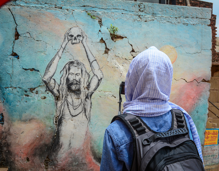 Varanasi, India - Jul 12, 2015. A tourist taking pictures about old wall in Varanasi, India. Varanasi is the holiest of the seven sacred cities (Sapta Puri) in Buddhism, Hinduism and Jainism. Editorial