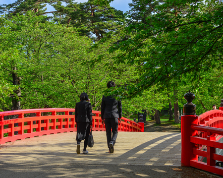 A couple walking on red bridge over the moat of Hirosaki Castle in Aomori, Japan.