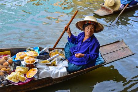 방콕, 태국 -6 월 19 일, 2017. 방콕, 태국에서 Damnoen 담넌 부동 시장에서 보트에 음식을 판매하는 여자. Damnoen Saduak는 태국에서 가장 인기있는 떠있는 시장