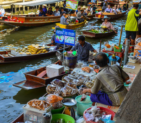 Bangkok, Thailand - Jun 19, 2017. Vendors selling food on wooden boat at Damnoen Saduak Floating Market in Bangkok, Thailand.