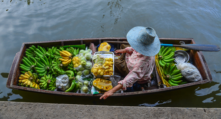 Bangkok, Thailand - Jun 19, 2017. A woman selling fruits at Damnoen Saduak Floating Market in Bangkok, Thailand. Damnoen Saduak is one of the most popular floating markets in Thailand.