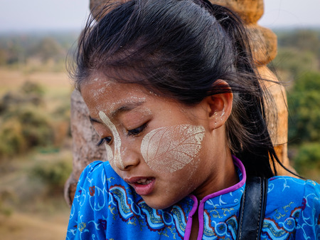Bagan, Myanmar - Feb 17, 2016. A Burmese girl with thanaka paste on her face in Bagan, Myanmar. Thanaka is a yellowish-white cosmetic paste made from ground bark.