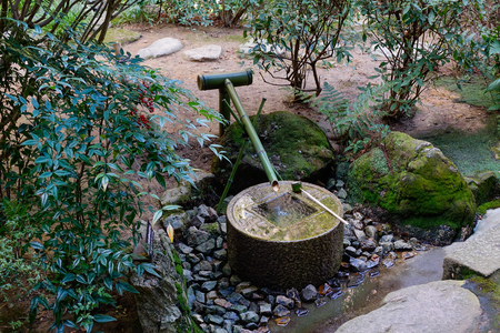 A tsukubai (washbasin) at a temple in Kyoto, Japan. The basin provided for ritual washing of the hands and mouth.