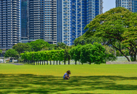 Manila, Philippines - Apr 13, 2017. A girl playing at Manila American Cemetery. Cemetery honors the American and allied servicemen who died in World War II. Editorial