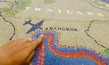 A hand on historic map of Thailand in a museum.