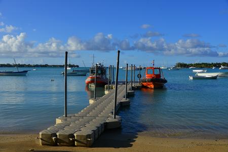 Grand Baie, Mauritius - Jan 9, 2017. Coast Guard ships docking at small pier in Grand Baie, Mauritius Island. Mauritius is a major tourist destination, ranking 3rd in the region. Editorial