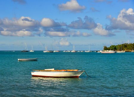 Grand Baie, Mauritius - Jan 9, 2017. Small boats on beautiful sea at sunny day in Grand Baie, Mauritius Island. Mauritius is 2,000 km off the southeast coast of Africa.
