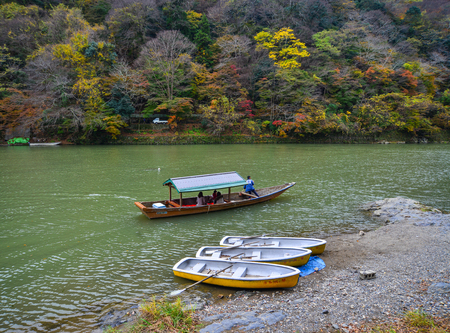 Kyoto, Japan - Nov 28, 2016. Tourist boats on Hozu River at Arashiyama in Kyoto, Japan. Arashiyama is a nationally designated Historic Site and Place of Scenic Beauty. Editorial