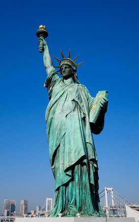 Replicas of the Statue of Liberty with cityscape background at Odaiba Park in Tokyo Japan.