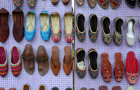 Colorful oriental ethnic shoes on flea market in Jaipur, India. Stock Photo