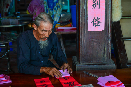 Vung Tau, Vietnam - Feb 6, 2018. An old man writing Chinese calligraphy on red paper at an old village in Vung Tau, Vietnam.