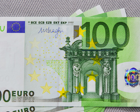 Group of Euro banknotes (100 EUR) on white background. Close up.