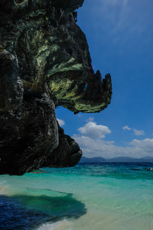 Black rock with beautiful blue sea at summer day in Palawan Island, Philippines.