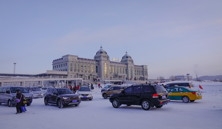 Mohe, China - Feb 19, 2017. Car parking lot of railway station at winter in Mohe County, Heilongjiang Province, China. Editorial
