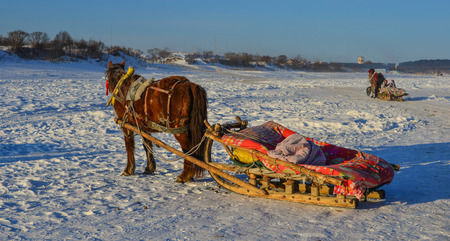 Mohe, China - Feb 20, 2017. Horse carts running on ice river in Mohe County, Heilongjiang Province, China. Editorial