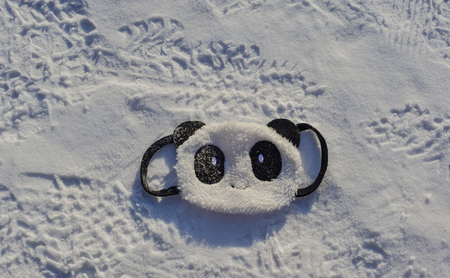 Cute panda mask on snow at winter in Mohe, China.