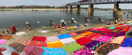 Agra, India - Jul 13, 2015. People washing colorful clothes on riverbank of Yamuna in Agra, India. Editorial
