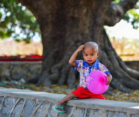Mandalay, Myanmar - Feb 11, 2017. A little boy playing with a balloon at the park in Mandalay, Myanmar.