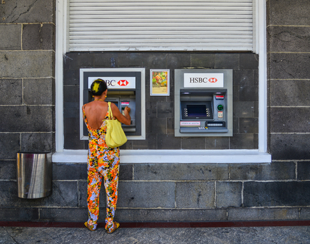 Port Louis, Mauritius - Jan 4, 2017. A woman withdrawing money at HSBC ATM machine in Port Louis, Mauritius.