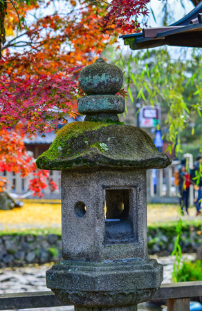 Japanese ancient stone lantern with autumn park background.