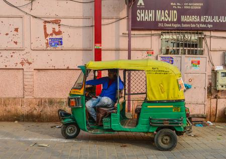 New Delhi, India - Nov 11, 2017. Private auto rickshaw three-weeler tuk-tuk taxi drives down the street in New Delhi, India.
